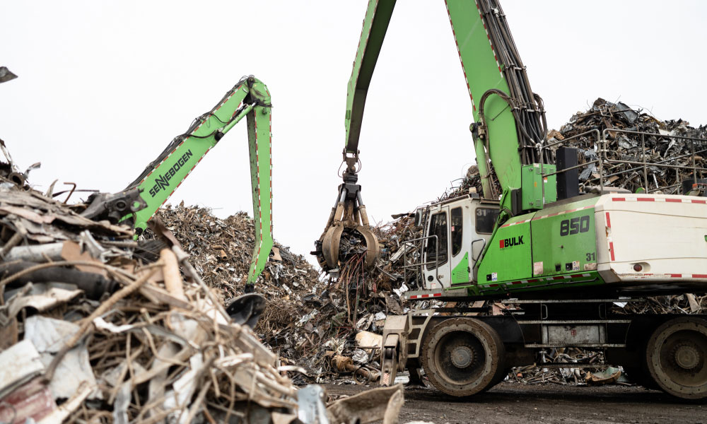 Green Sennebogen 850 Material Handler Lifting Steel Scraps