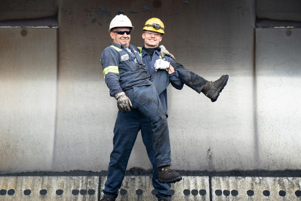 Bulk Team Member Carrying Fellow Member Both Wearing PPE