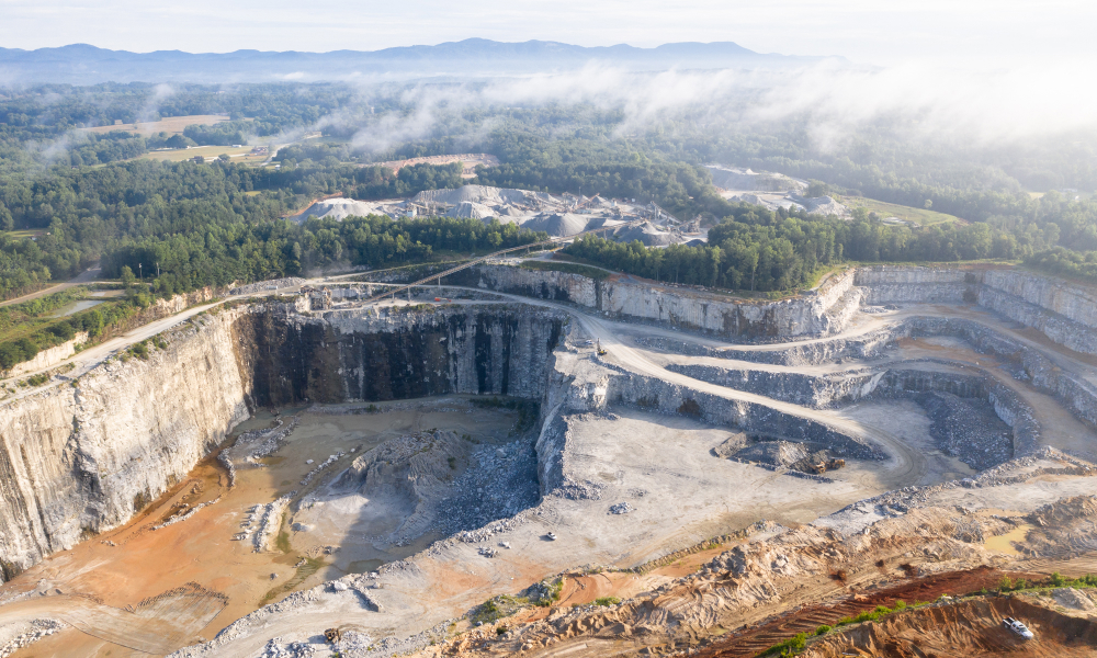 Aerial View of a Quarry & Mining Site With Trees and Mountains In the Distance